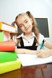 School girl sitting at the table with books. Royalty Free Stock Image