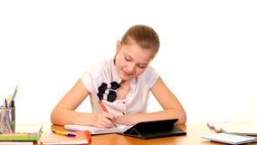 School girl sitting, thinking and writing homework stock video footage