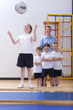 School girl standing on bench and catching ball in school gymnasium with teacher and classmates watching Stock Images