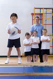School girl standing on bench and holding ball in school gymnasium with teacher and classmates watching Royalty Free Stock Image