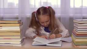 School girl at table thinking about homework and writing in a school notebook. Portrait school girl at table thinking about homework and writing in a school stock footage