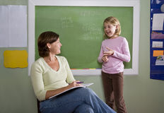 School girl and teacher by blackboard in classroom Stock Images