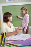 School girl and teacher by blackboard in classroom