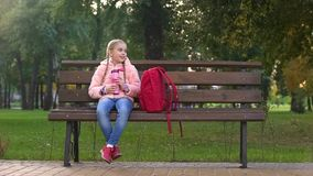 School girl with thermos sitting on bench, resting after hard day in fall park royalty free stock photography