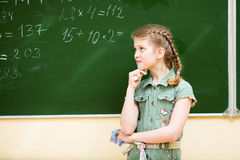 School girl thinking at blackboard Stock Image