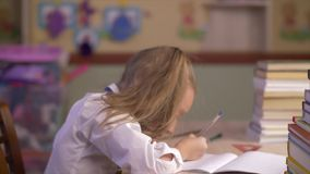 School girl thinking and making homework and writing new idea in school notebook. Serious school girl thinking and making homework at table side view. Happy stock footage