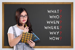 School girl thinking 5W1H. Thoughtful school girl looking at 5W1H analysis written on blackboard: what, who, when, where, why, how Stock Photography