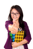 School girl thumb up isolated. Portrait of attractive Asian girl holding books and giving a thumb up, isolated on white background Stock Images