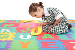 School girl in uniform and alphabet letter puzzle. Girl in uniform finishing alphabet letter puzzle. Isolated on white Stock Photo