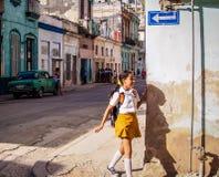 School girl in Havana. School girl in school uniform runs around a corner casting a shadow Royalty Free Stock Photography