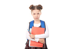 School girl unwilling to study. Portrait of displeased girl in school uniform with backpack holding textbooks and pencils against white background Royalty Free Stock Image