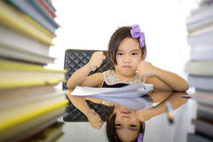 School girl wearing an overall doing homework Royalty Free Stock Photography