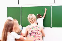 School girl writes on the blackboard. In class sitting other students and a teacher and look at the board Royalty Free Stock Image