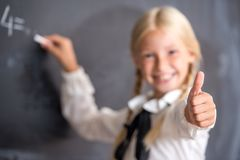 School girl writing on blackboard. Close up of little school girl writing on blackboard and showing thumb up in classroom Royalty Free Stock Images