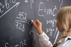 School girl writing on blackboard. Little school girl writing on blackboard in classroom Royalty Free Stock Photo