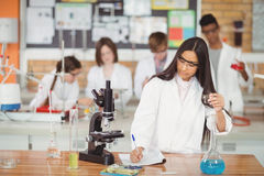 School girl writing in journal book while experimenting in laboratory Royalty Free Stock Photo