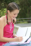 School GIrl writing in Notebook Outdoors Royalty Free Stock Images