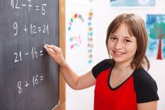 School girl writing solution on chalkboard. Happy elementary schoolgirl writing equation solution on chalkboard Stock Photos