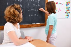 School girl writing solution on chalkboard. Elementary school girl writing equation solution on chalkboard, teacher looking at her (focus on black baord Royalty Free Stock Photo