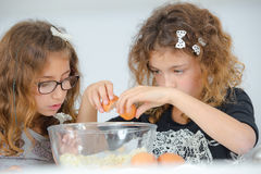 School girls breaking eggs into bowl Stock Images