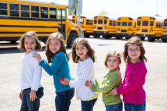 School girls friends in a row walking from school bus. School girls friends sisters in a row walking from yellow school bus lot Royalty Free Stock Photo