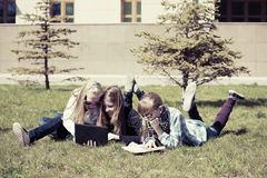 School girls lying on the grass in campus Stock Photos
