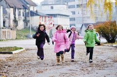 School girls running away. Happy school girls running outdoor at sunny autumn day Royalty Free Stock Photo