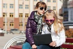 School girls using laptop on the bench. Teenage schoolgirls using laptop on the bench Stock Photo