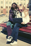 School girls using laptop on the bench. Two school girls using laptop on the bench Royalty Free Stock Photography