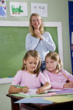 School girls writing in notebooks with teacher Royalty Free Stock Photo