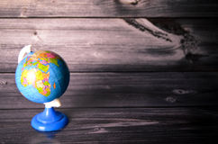 School globe. In front of a wooden background Royalty Free Stock Photography