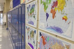 School Hallway with Maps. A brightly lit reflective school hallway with a glass exit door at the far end, and lined with metal blue lockers and colorful maps stock photo