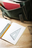 School Homework. A school satchel on a wooden table, behind an open exercise book with maths equipment Royalty Free Stock Image