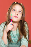 School homework. Young schoolgirl holding a pen and thinking Stock Photography