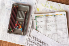 School homework. Looking down on colored pencils, schedule book and home work from middle school student stock images