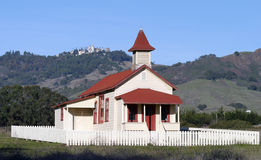 School House and Castle. An old schoolhouse in an open field with a castle on the mountains in the background Stock Photo