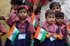 School Independence Day celebration by kids. Little kids in school uniform celebrate Indian Independence Day holding national flag or tricolor. Event of Kendriya Royalty Free Stock Photo