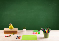School items on desk with empty chalkboard Stock Photos