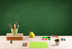 School items on desk with empty chalkboard Royalty Free Stock Image