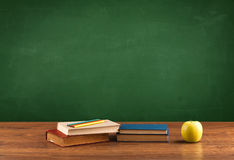 School items on desk with empty chalkboard Stock Images