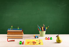 School items on desk with empty chalkboard Stock Photography