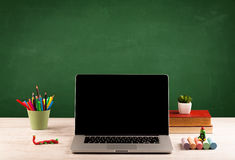 School items on desk with empty chalkboard stock image