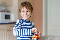 School kid boy playing with lots of small colorful plastic block stock photography