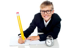 School kid finishing his assignment in time. Casual shot of a school kid wearing spectacles finishing his assignment in time Royalty Free Stock Photography
