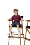 School kid sitting on director's chair over white background Stock Photos