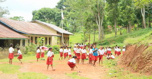 School kids. Girls and boys playing barefoot on school yard in school uniforms neer by Labuan Bajo (Flores, Indonesia Royalty Free Stock Image