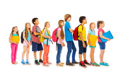 School kids with backpacks and textbooks. Happy children standing in a line holding textbooks isolated on white side view Stock Photography