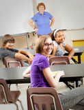 School Kids in Class. Portrait of teenage students and their teacher in the classroom.  Focus on the girl in the front with glasses Stock Photography