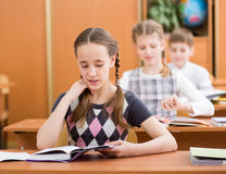 School kids in classroom at lesson. Schoolkids in classroom. Girl reading task aloud at lesson Stock Images