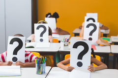 School kids covering their face with question mark sign. In classroom at school Royalty Free Stock Photography